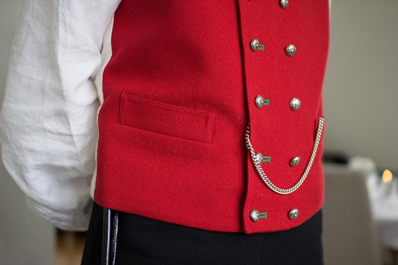 Nærbilde av rød vest til Sunnhordlandsbunad til herre. Dobbeltspent med sølvknapper.
